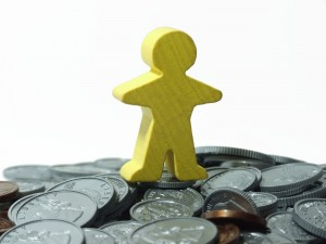 monigote montado en monton de monedas